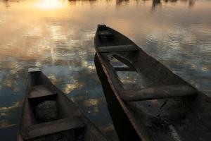 Sunlight and Clouds Reflecting in Calm Water Near Canoes by Cristina Mittermeier
