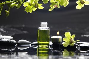 Tranquil Spa Scene - Massage Oil and Candle on Black Stones with Green Orchid by crystalfoto
