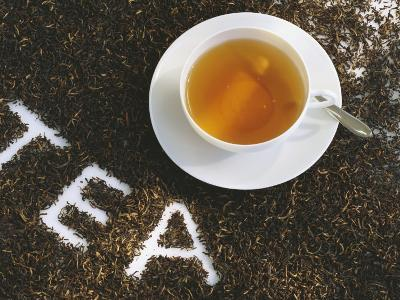 Cup of Black Tea, Surrounded by Tea Leaves with the Word Tea--Photographic Print
