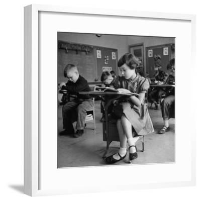 Cute Little Girl Busily at Work, Sitting in a Desk Chair in a Schoolroom, Other Pupils at Work Too-Gordon Parks-Framed Premium Photographic Print