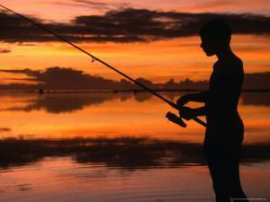 The Silhouette of a Boy Fishing at Sunset in One of the Lagoons Around the Island, Cook Islands by Dallas Stribley