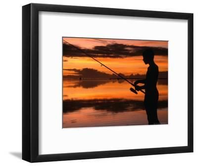 The Silhouette of a Boy Fishing at Sunset in One of the Lagoons Around the Island, Cook Islands