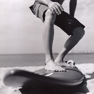 Young Man Standing on Surfboard on the Beach by Daniel Attia