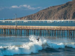 A Central Coast Surfer Takes Off On A Wave In Avila Beach, California by Daniel Kuras