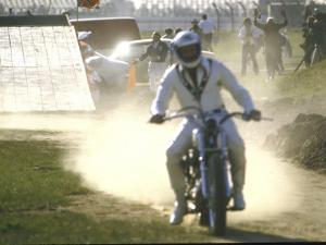 Daredevil Motorcyclist Evel Knievel Raising Dust after Completing Stunt