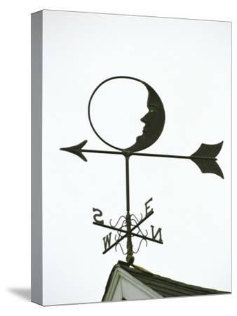 A Man-In-The-Moon Weather Vane on a Roof Top
