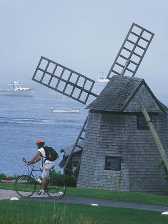 Bicyclist Rides Past a Windmill on a Cape Cod Shore, Chatham, Massachusetts
