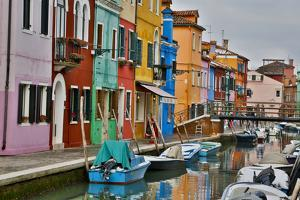 Boats Docked Along Canal with the Colorful Homes of Burano, Italy by Darrell Gulin
