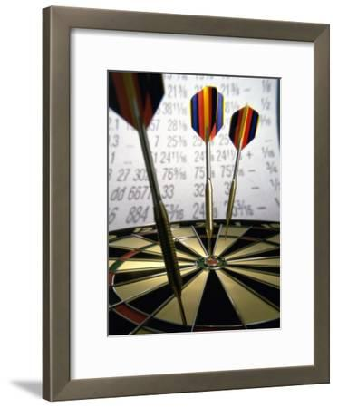 Darts on a Dartboard with Stock Figures in the Background