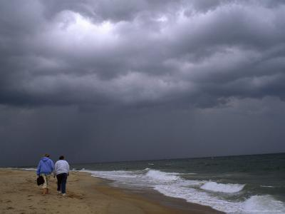 Daughter and Mother Walk Along a Beach, Storm Clouds Darken the Sky-Brian Gordon Green-Photographic Print