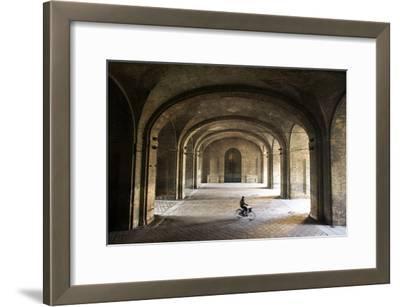 A Bicyclist Passes Through Archways in Palazzo Della Pilotta