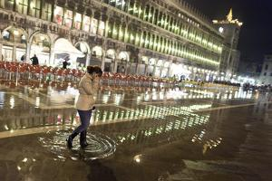 A Woman Walks in Piazza San Marco During High Tide in Venice, Italy by Dave Yoder