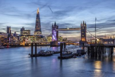 The Tower Bridge in London Seen from the East at Dusk. in the Background by David Bank