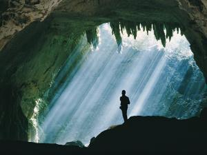 A Man Stands Below the Mouth of a Giant Cave by David Boyer