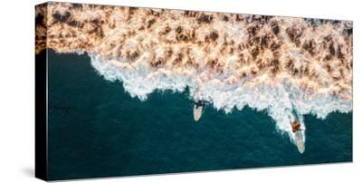 Aerial drone photo of surfers riding Pacific Ocean waves in San Diego, California at Sunset Cliffs
