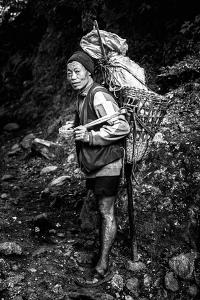 Black and white picture of a Sherpa carrying meat up to Everest Base Camp in Nepal by David Chang