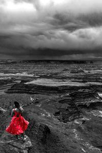 Dark storm clouds over Dead Horse Point State Park with girl in red dress standing near the cliff by David Chang