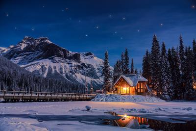 Emerald Lake Lodge in Banff, Canada during winter with snow and mountains at night with starry sky