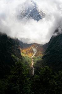 Giant mountain emerging through the clouds in the Himalayas, Nepal on the way to Everest Base Camp by David Chang