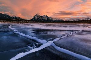 Ice cracks along Abraham Lake in Banff, Canada at sunset with pink clouds and scenic mountains by David Chang