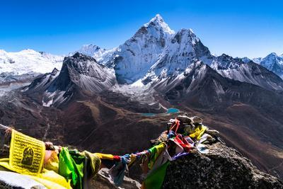 Prayer flags in Himalayas, Nepal with Ama Dablam mountain from high elevation with snow and lake