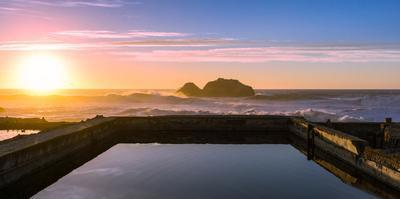 Sunset at Sutro Baths with water reflection in San Francisco with Pacific Ocean waves breaking by David Chang