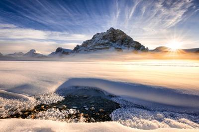 Sunset over mountains at Bow Lake in Banff, Canada during the winter with snow and blue skies by David Chang