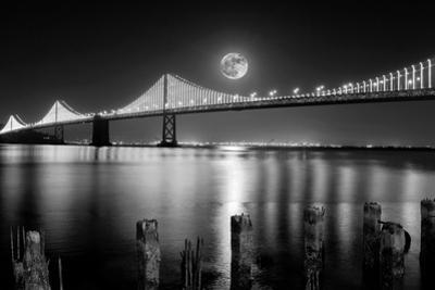 Super full moon rising in San Francisco Embarcadero pier over the Bay Bridge in the evening by David Chang