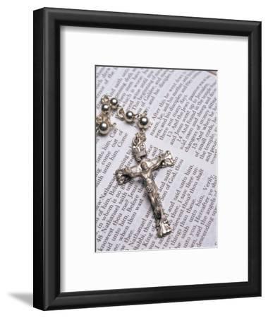 Silver Crucifix Lying on Open Bible