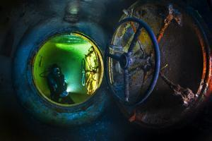 A diver explores the USS Kittiwake wreck sunk as an artificial reef. by David Doubilet