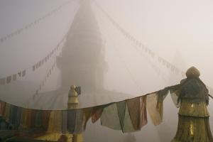 A temple and prayer flags shrouded in fog. by David Edwards
