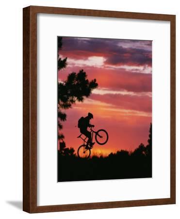 Silhouetted Biker Pulls a Wheelie at Twilight