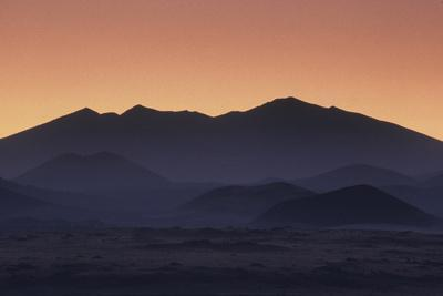 Volcanic Cones in Northern Arizona, are Illuminated Purple at Dawn