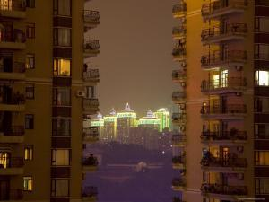 Neon Outlined Buildings in Distance Behind Balconied Apartment Blocks, Chongqing, China by David Evans