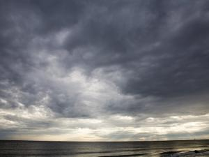 Sun Streams Through Gathering Storm Clouds on North Carolina Coast by David Evans
