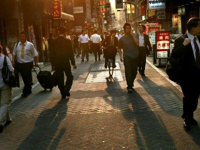 Japanese Commuters Walk Through a Tokyo Street on Their Way to the Train Stations