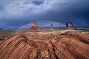 A Rainbow Arcs over West Mitten, Closer, East Mitten and Merrick Butte, on the Right by David Hiser