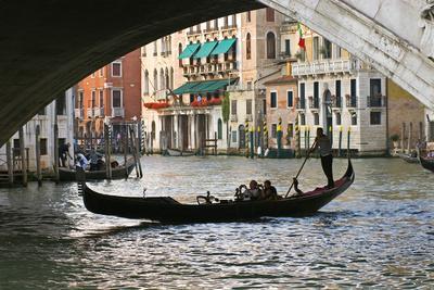 Tourist in a Gondola as They Pass under the Rialto Bridge, Venice, Italy