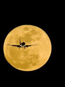 Aeroplane Silhouetted Against a Full Moon by David Nunuk