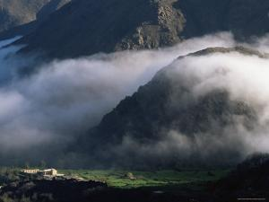 Local School Below Mist Rising in Valley of the High Atlas Mountains, Morocco, North Africa, Africa by David Poole