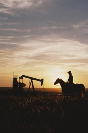 Old West, New West, Man Sitting on Horse with Oil Refinery at Sunset by David R^ Frazier
