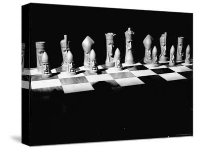 View Showing Chess Pieces with Faces Carved Into Them
