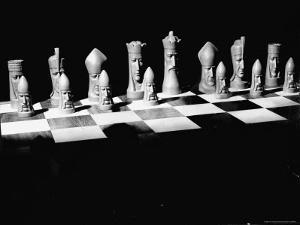 View Showing Chess Pieces with Faces Carved Into Them by David Scherman