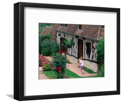 Child with Baguettes in Front of Half-Timbered Cottage