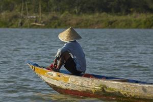 Man fishing from boat on Thu Bon River, Hoi An, Vietnam by David Wall