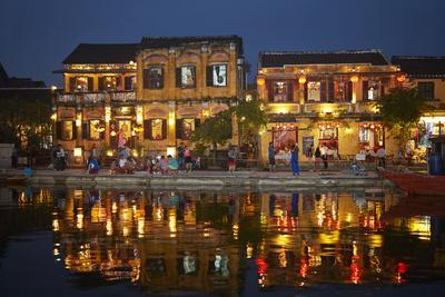 Restaurants and tourists reflected in Thu Bon River at dusk, Hoi An, Vietnam