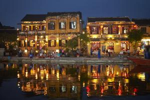 Restaurants and tourists reflected in Thu Bon River at dusk, Hoi An, Vietnam by David Wall