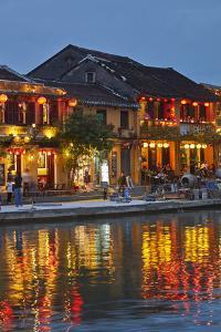 Restaurants reflected in Thu Bon River at dusk, Hoi An, Vietnam by David Wall