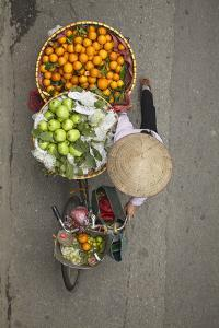 Street vendor with baskets of fruit on bicycle, Old Quarter, Hanoi, Vietnam by David Wall