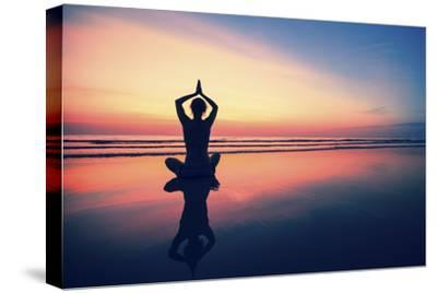 Woman Practicing Yoga on the Sea Beach at Surrealistic Sunset.